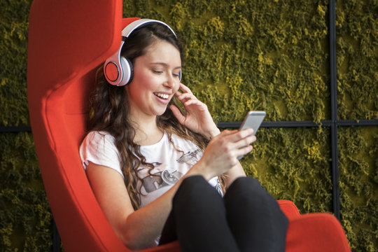 Young woman listening to music in modern chair
