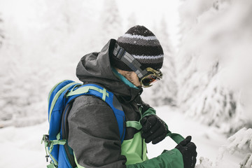 Side view of man fastening belt while standing on snow covered field