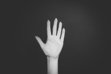 Woman hand  showing the five fingers isolated on the black background