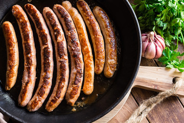 Fried sausages with golden crust in iron cast pan, garlic and fresh parsley on wood kitchen table, top view, cooking concept