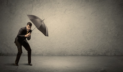 Handsome business man holding umbrella with copy space background
