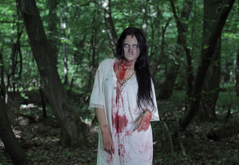 Zombie girl in a white nightgown in the forest.