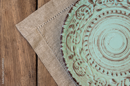 empty vintage relief plate on linen napkin on plank wood table top
