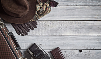 Man's hat and retro accessories for travel on a white painted wo