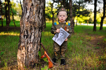 Child boy in military uniform of a Soviet soldier with a photograph of a veteran of World War II in hands against a background of green trees. Victory Day, May 9, against fascism.