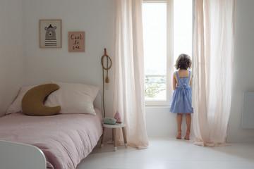 petite fille qui regarde par la fenêtre dans sa chambre