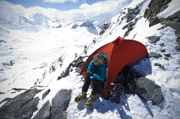 A mountaineer enjoys the view camping at high altitude on a mountain