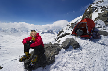 A female mountaineer camping at high altitude smiles and enjoys herself.