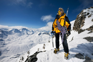 A mountaineer stating in her crampons with ice axes and ropes pauses to look at the incredible view. Wall mural