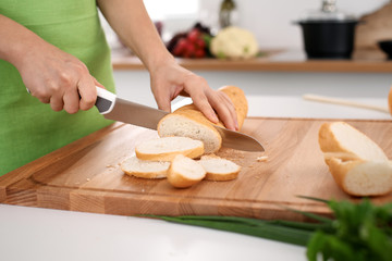 Close up of  woman's hands cooking in the kitchen. Housewife slicing white bread. Vegetarian and healthily cooking concept
