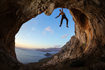 Rock climber gripping handhold on ceiling in cave