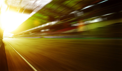 Wall Mural - Foward motion speed lens blur racing circuit background with seated stand , sunset scene  .