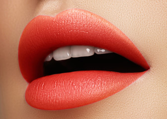 Cosmetics, makeup. Bright lipstick on lips. Closeup of beautiful female mouth with red and pink lip makeup. Part of face