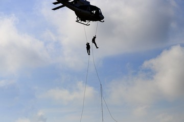 silhouette Soldier rappelling from helicopter in blue sky