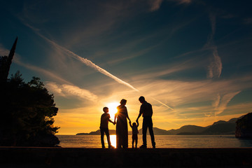 Silhouette of parents and two children at sea at sunset. Montenegro, the Adriatic.