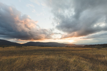 Cloudy Sunset Over Mountains and Field