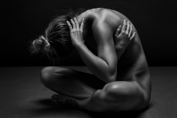 Athletic Naked woman body on black background. Fine art photo of female body.