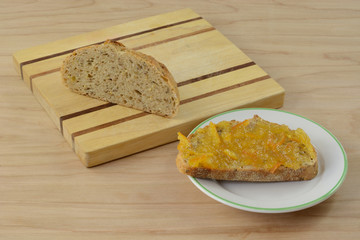 Orange marmalade on piece of toast and remaining nine gain loaf on wooden cutting board