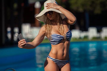 Portrait of beautiful young girl who is taking a selfie at the swimming pool.