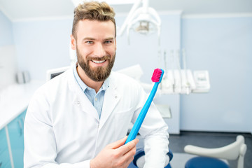 Portrait of funny dentist in uniform with big toothbrush at the dental office