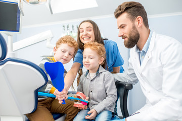 Young boys looking at the mirror with toothy smile sitting with dentist and woman assistant at the dental office