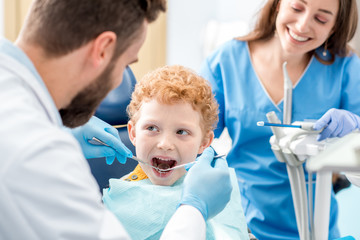Children's dentist and assistant examinating baby teeth of a young boy sitting on the dental chair at the office