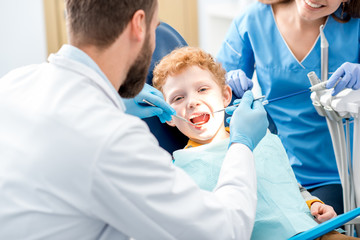 Children's dentist examinating baby teeth of a young boy sitting on the dental chair at the office