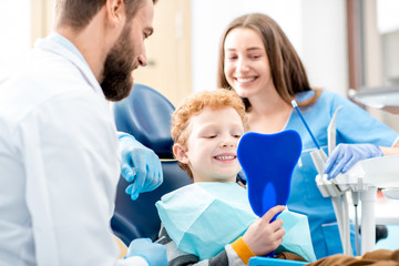Young boy looking at the mirror with toothy smile sitting on the chair with dentist and assistant at the dental office