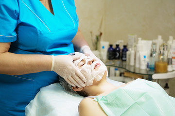 Young woman In Spa Salon With Facial Mask