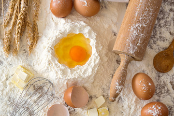eggs, dough, flour and rolling-pin baking cakes on wooden table.