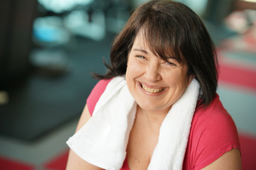 Portrait of cheerful overweight woman at the gym