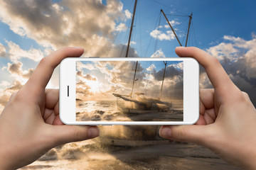 Female hands with a smartphone close-up. Photographing a ship and a storm in the sea at sunset