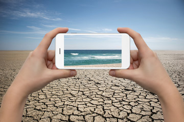Hands with phone on desert background. On the screen the sea. Concept