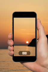 Female hands with a smartphone close-up. Photographing the sunset in the sea
