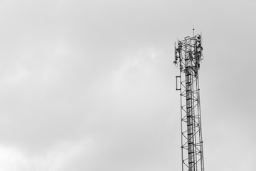 Tower with data transmission equipment on sky background - black and white