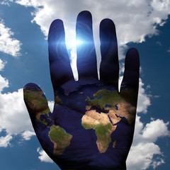 Earth on Hand with sky background  Some elements provided courtesy of NASA