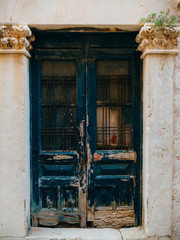 Old blue doors. Wood texture. Texture of metal. Old shabby, irradiated paint