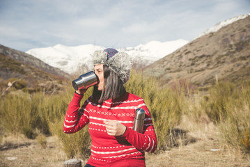 Woman smiling and enjoying at the sun in the nature with a thermo