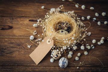 Easter quail eggs in nest over wooden background