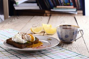 eggs pashot on a toast and tea with lemon