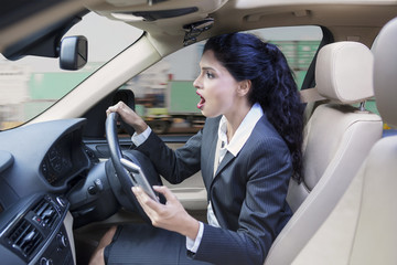 Businesswoman with cellphone driving car