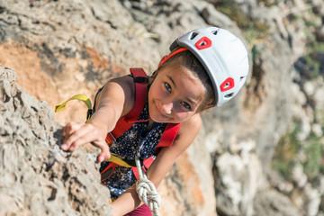 Little Child in protective Helmet climbing Rock