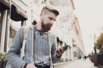 Outdoor portrait of modern young traveler man using smart phone on the street