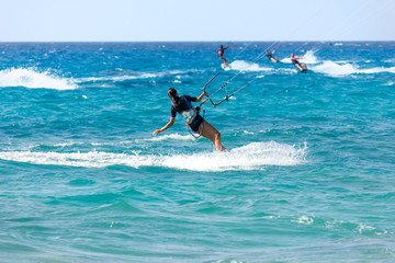 A young woman kite-surfer rides in summer day