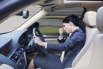 Frustrated businesswoman driving car