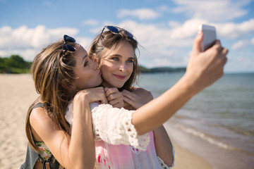 Two beautiful female friends taking selfie on beach having fun