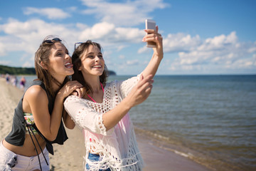 Two happy girls taking selfie on beach having fun