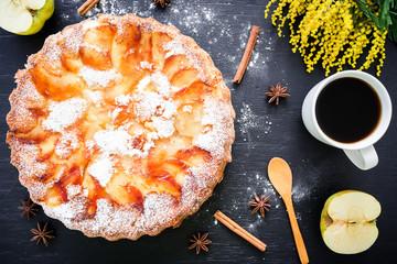 Sweet cake, coffee mug, apple, cinnamon and mimosa flowers on dark background. Flat lay, Top view. Food background