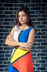 Beautiful serious teen girl wearing colorful dress standing with hands crossed