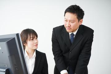 若いビジネスウーマンと指導をする上司の男性